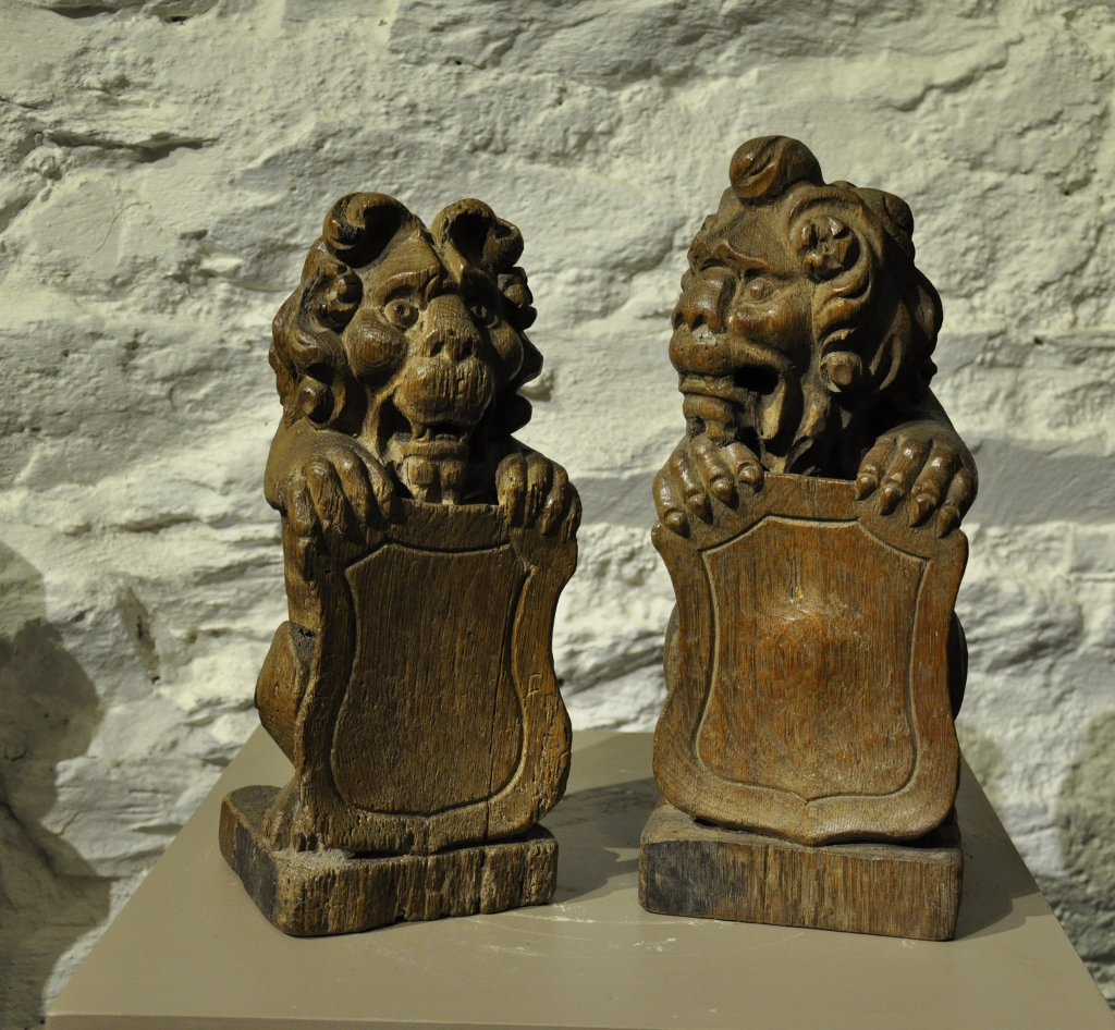 AN ATTRACTIVE PAIR OF LATE 16TH / EARLY 17TH CENTURY ENGLISH CARVED OAK LION FINIALS.