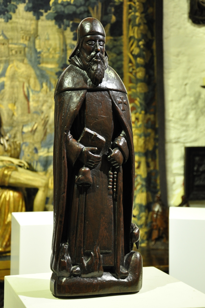 AN EXTREMELY RARE PRE-REFORMATION ENGLISH YEW WOOD SCULPTURE OF ST ANTHONY. CIRCA 1450.